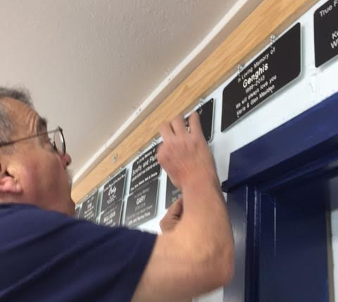Memorial Plaque being hung by volunteer Rod Vetter